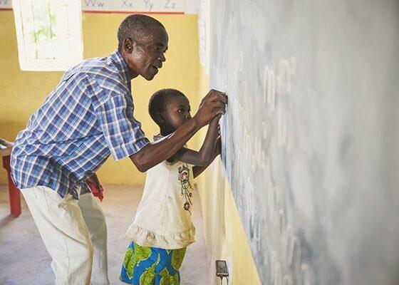 teacher helping student at a chalkboard in a rural school in Zambia