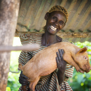 A woman in Uganda holds a pig that she received from a Bright Hope partner church through a family empowerment initiative.